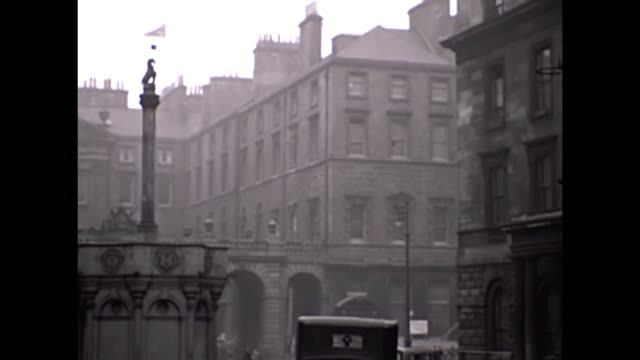 views of st giles' cathedral, statue and doorway . views of the adjacent street , vehicles and people . - 1930点の映像素材/bロール