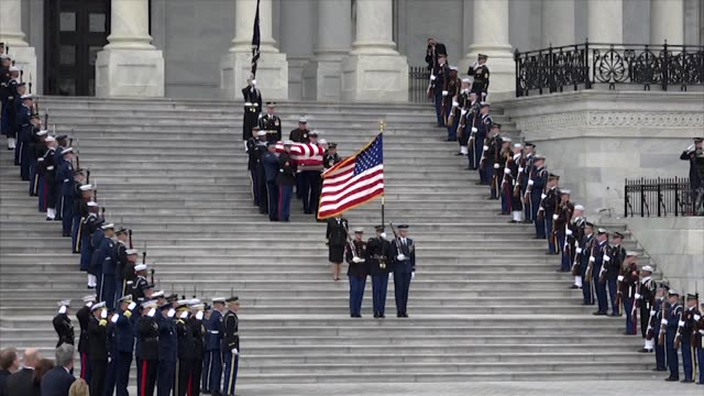 Views of the Capitol dome George W Bush stepping out of a vehicle an American flag Congressional leaders with spouses a military honor guard and pall...