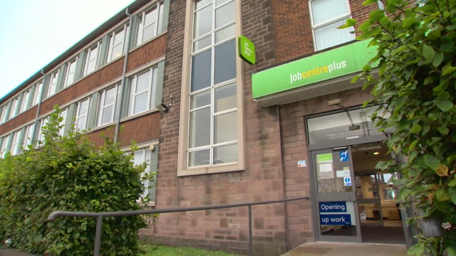 views of the front of a job centre with a universal credit sign in the window - soziale fürsorge stock-videos und b-roll-filmmaterial