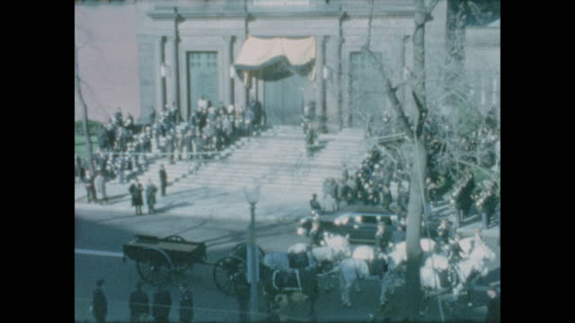 views of the large crowds gathered in front of the cathedral of st. matthew the apostle for jfk's funeral service. zoomed in jfk's empty horse drawn... - 使徒点の映像素材/bロール