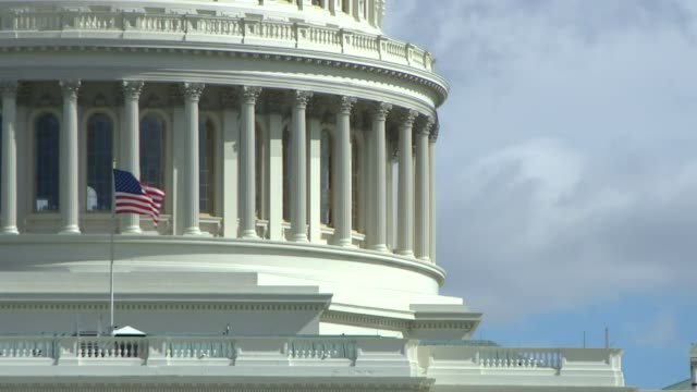 views of the us flag waving on the us capitol building - capitol building stock videos & royalty-free footage