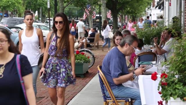 vídeos de stock e filmes b-roll de views of the village center street as people eat at outdoor restaurants in southampton ny, july 22-23, 2017. photographer: timothy fadek - shots: pan... - shopping centre