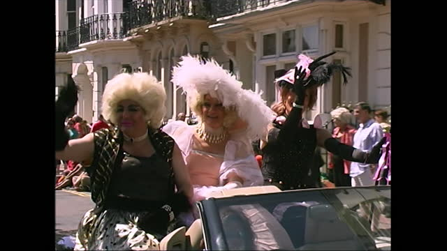 views of three people wearing pink and black dresses with feathery hats as they take part in the pride parade in brighton, uk; 2000. - adult stock videos & royalty-free footage
