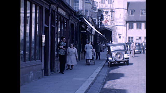 views of wells market place with cars and pedestrians / the cathedral / tailors outfitters shop - wells cathedral stock videos & royalty-free footage
