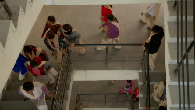 Views of young women walking up and down stairs in a college building, Patna, India.