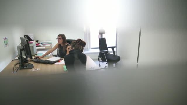vídeos de stock, filmes e b-roll de views through the blind slats of a consultation room show back view of a female jobseeker speaking to an employee inside a pole emploi job center the... - procurando emprego trabalho e emprego
