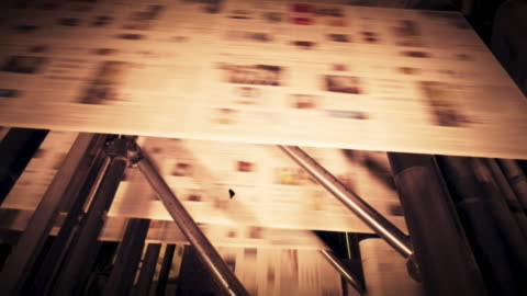 cs vignette: sheet of freshly printed newspaper moving through the machine in the printing factory - vignette stock videos & royalty-free footage