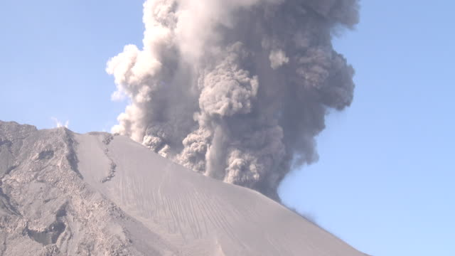 vídeos de stock, filmes e b-roll de vigorous ash venting from the active crater at sakurajima volcano in japan send ash and rocks into the air - send
