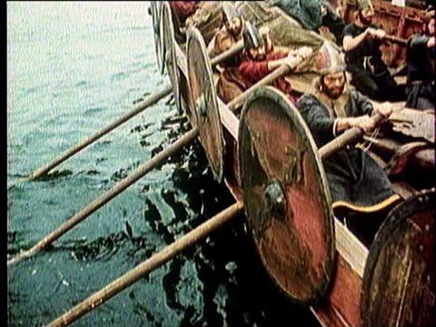 1965 reenactment montage viking longship sailing with a crew of helmeted oarsman rowing in unison in ocean off coast  - viking stock videos and b-roll footage