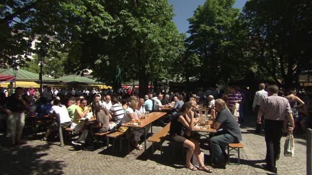 viktualienmarkt, biergarten, people, panning shot, blue skay, green trees - marktstand stock-videos und b-roll-filmmaterial