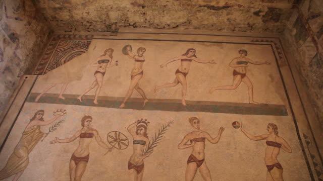 vídeos de stock e filmes b-roll de villa romana del casale, roman mosaics in the roman villa near piazza armerina - figura feminina