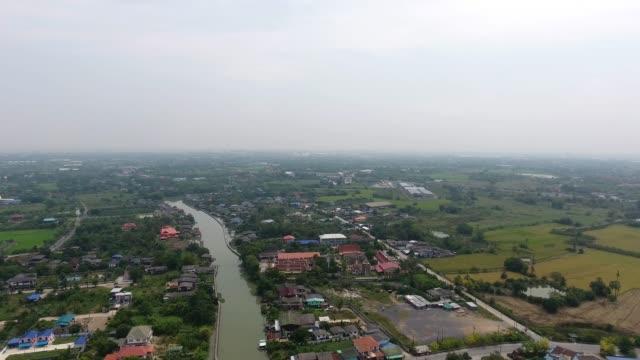 vídeos y material grabado en eventos de stock de pueblo, vista aérea de estilo tailandés de la casa a lo largo del canal. - mckyartstudio