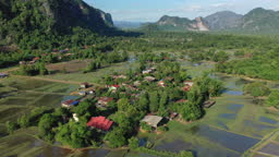A village in the middle of rice paddies, forests and mountains in Laos, in summer, by drone on a beautiful sunny day.