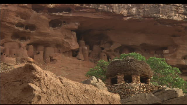 a village lies nestled under a desert ledge, mali. available in hd. - mud stock videos & royalty-free footage