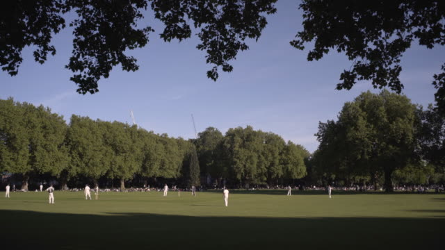 """village london"" afternoon cricket in the the london fields park. hackney - cricket video stock e b–roll"