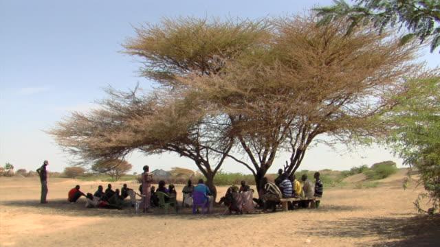 ms village meeting under tree / nackhukui, turkana, kenya - village stock videos & royalty-free footage