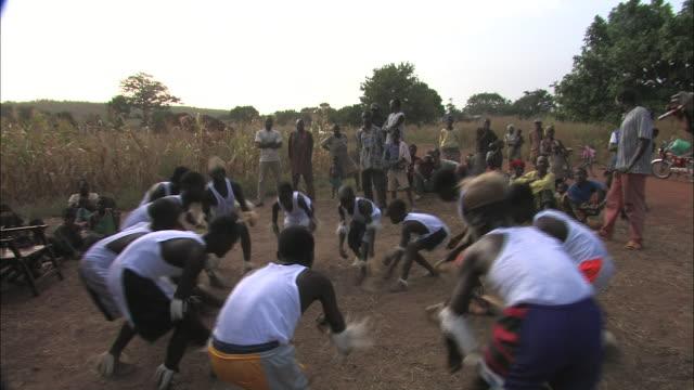 stockvideo's en b-roll-footage met village men perform a tribal dance at the edge of a corn field. - men