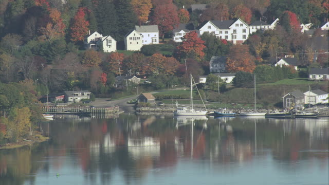 aerial village nestled among fall colored trees with sailboats anchored and reflected in calm water / cushing, maine, united states - anchored stock videos & royalty-free footage