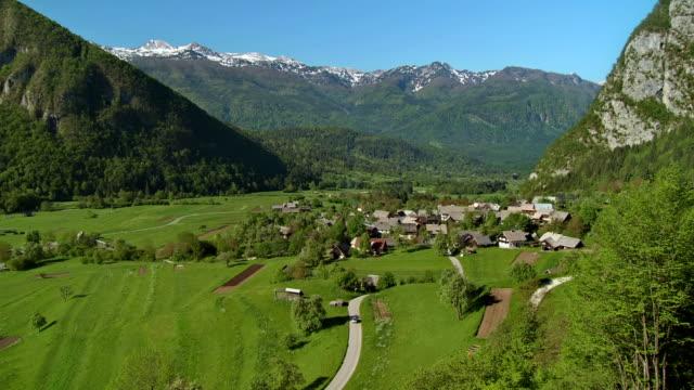 ws tu village of studor with julian alps in the background / bohinj, triglav national park, slovenia - julian alps stock videos and b-roll footage