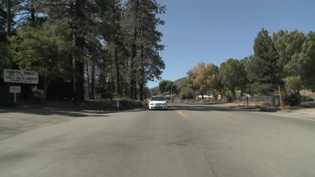 ws pov village of traffic on highway / wrightwood, california, usa   - 乗物後部から見た視点点の映像素材/bロール