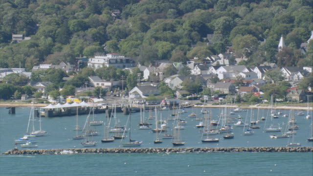 aerial village on hilly shoreline, with protected harbor enclosing many anchored sailboats / vineyard haven, massachusetts, united states - anchored stock videos & royalty-free footage