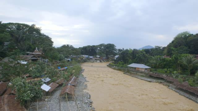 vídeos de stock e filmes b-roll de ms village on river with rope bridge / bukit lawang, north sumatra, indonesia - ponte suspensa