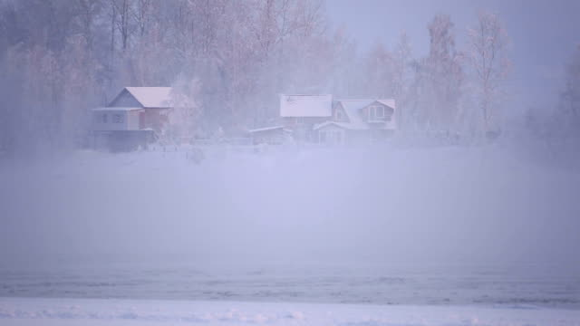 Village on the banks of the river in a frosty mist.