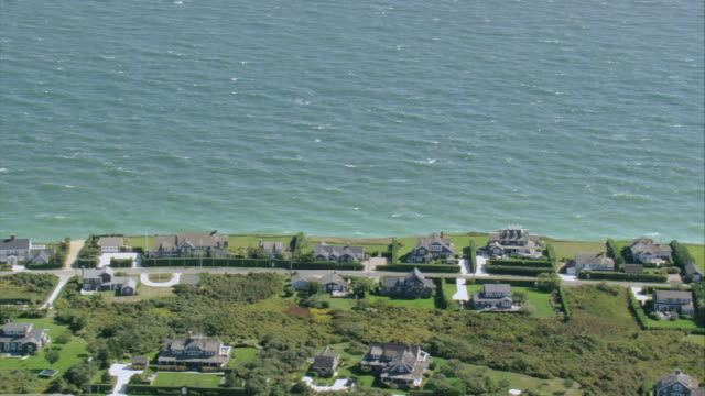 AERIAL Village on the shoreline with narrow sandy beach and blue water / Nantucket, Massachusetts, United States