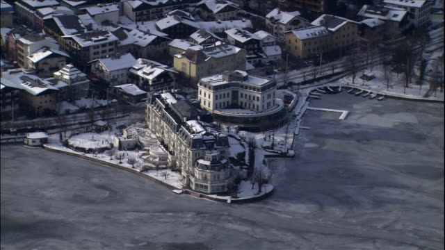 A village sits at the edge of a frozen lake at the foot of a mountain in Zell Am See, Austria.