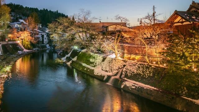 vídeos de stock, filmes e b-roll de crepúsculo-sol de vila neve vista na cidade de takayama e água de fluxo, lapso de tempo no japão - vista da cidade