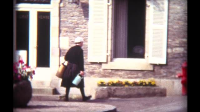 1973 village woman with milk jug - bretagna video stock e b–roll