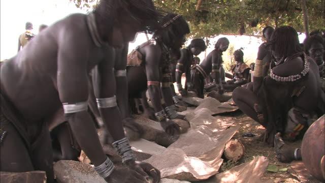 village women grind sorghum. - sorghum stock videos & royalty-free footage