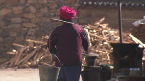 vídeos y material grabado en eventos de stock de a villager carries water on a pole across her shoulders. - cargar