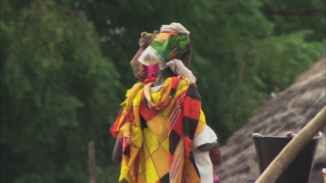 ts a villager carrying a basket on her head past thatched huts / dakar, senegal - head stock videos & royalty-free footage
