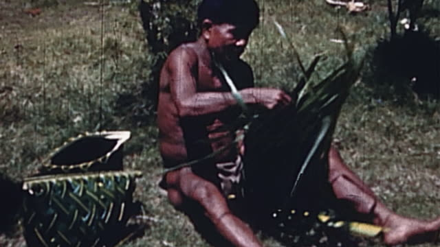 ha villager sitting on ground weaving basket of palm fronds on a pacific island during wwii - blattfiedern stock-videos und b-roll-filmmaterial
