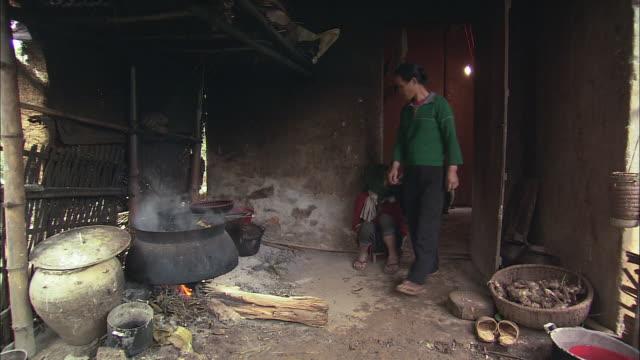 vídeos y material grabado en eventos de stock de zi villager tending a fire under a large pot then ladling water into a smaller pot / ba bay, ba ria-vung tau, vietnam - cucharón