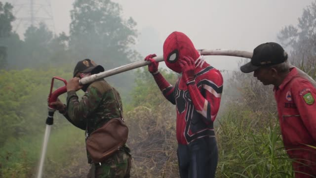 villager wearing a superhero costume tries to extinguish fires in riau, indonesia, on september 12, 2019. forest fires have razed hundreds of... - held stock-videos und b-roll-filmmaterial