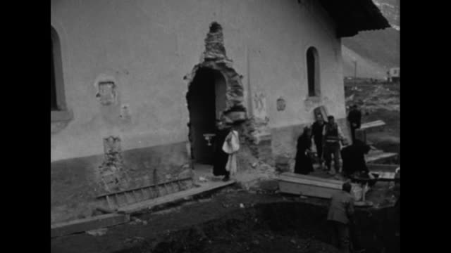vidéos et rushes de villagers and a priest remove sacred objects from st jacques de tarentaise church with large hole in its side / man stacks chair to be removed and... - prêtre