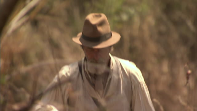 vídeos de stock e filmes b-roll de villagers carrying equipment follow behind an explorer. - exploração