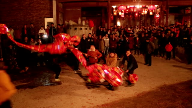 vídeos y material grabado en eventos de stock de fuzhou, china - february 11, 2017: villagers celebrate chinese new year by playing the dragon lantern at night. - dragon chino