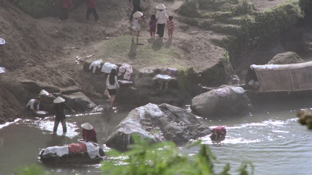 villagers do their laundry and bathe in a river. - riverbank stock videos & royalty-free footage