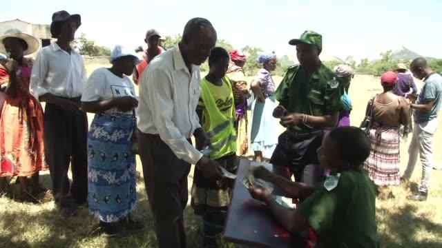 stockvideo's en b-roll-footage met villagers in mutoko zimbabwe receive cash donations in united states dollars and porridge for their children as part of an on going effort to fight... - hongerig