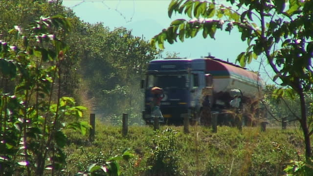 ws villagers in orchard moving past tanker truck / countryside, malawi - 2006 stock videos & royalty-free footage