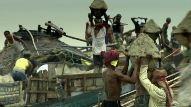 villagers living on the banks of the river padma (known in india as the ganges), which here are being rapidly eroded, work together to bring sand ashore that will be used to create sandbags in an effort to stop the erosion, bangladesh. - sandbag stock videos and b-roll footage