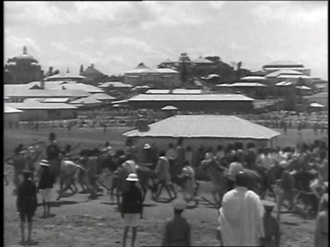 stockvideo's en b-roll-footage met villagers marching and on horseback as small crowd watches them pass / oxen and camels walking with loads - 1935