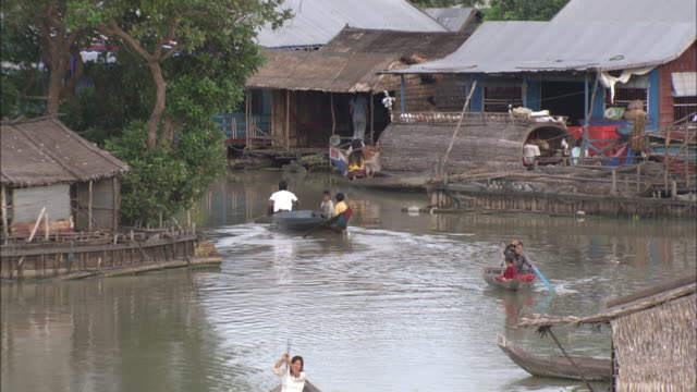 villagers paddle canoes through a village. - 掘建て小屋点の映像素材/bロール