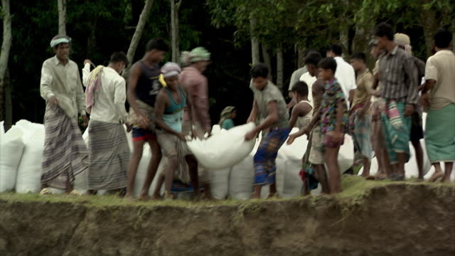 Villagers throw sandbags into the Padma River (known as the Ganges in India) in an attempt to shore up the riverbank against soil breaking away as part of rapid erosion suspected to be caused by climate change, Bangladesh.