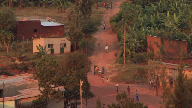 Villagers walk along a red drit road in Rwinkwavu, Rwanda.