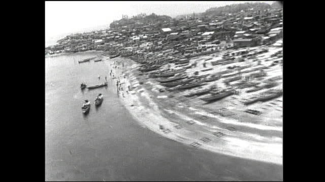 villagers walk along the shore at tokyo bay where fishing boats are anchored. - tokyo bay stock videos and b-roll footage