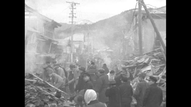 vs villagers walk amid collapsed ruins / people poking thought smoldering rubble / wide shot of villagers and debris - 1930~1939年点の映像素材/bロール